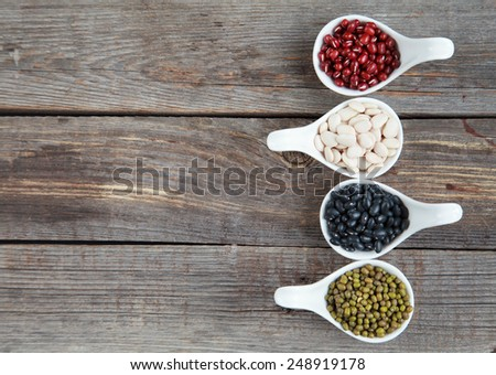 Set of different varieties of beans: baby lima, black small, adzuki and  mung in white ceramic spoons (appetizers) on wooden background, selective focus on beans - stock photo
