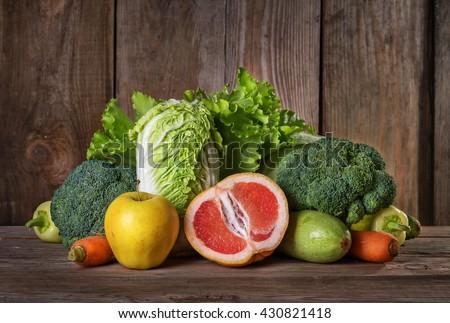 Set of different vegan foods on the old wooden background, vegetables, fruit, vegetarian concept - stock photo