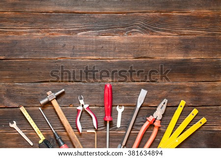Set of different work tools: screwdriver, pliers, hammer, pliers, handsaw, meter, wrench and other tools over dark wooden background.  - stock photo