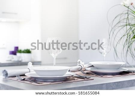 Set of dinner plates in modern, white kitchen  - stock photo
