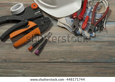 Set of electrical tools on wooden background. Accessories for engineering work, energy concept - stock photo