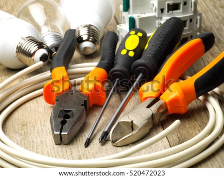 set of electrician tools, a coil of wire and equipment in background