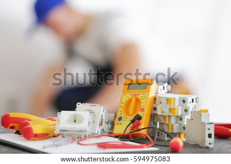 Set of electrician tools and blurred man at work on background