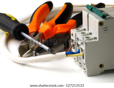 set of electrician tools and equipment and a coil of wire on a white background