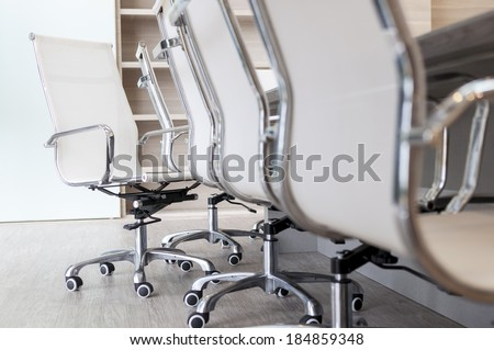 Set of empty office chairs next to long table in boardroom with low camera angle - stock photo