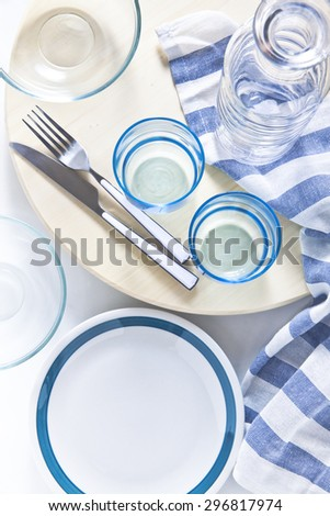 set of empty plates, glasses and cutlery set. blue striped napkin. pitcher for water or wine. on a light blue background. - stock photo