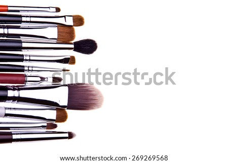 Set of essential professional make-up brushes are isolated with shadows on white background. Overhead view. Front part. Place for your text.  - stock photo