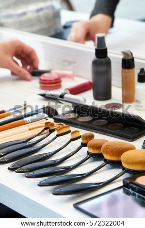 Set of expensive professional brushes for make-up. Many different cosmetics and brushes on a table in the salon. Work in a beauty salon. Work Desk of makeup artist in the studio.