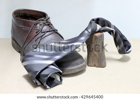Set of fashionable man's accessories, brown boots and gray and black striped necktie on wooden background. - Happy Fathers Day - stock photo