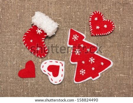 set of felt handmade Christmas decorations on sacking  - stock photo