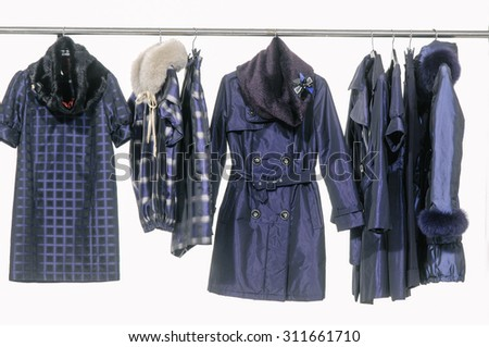Set of female dress with coat isolated on hanging