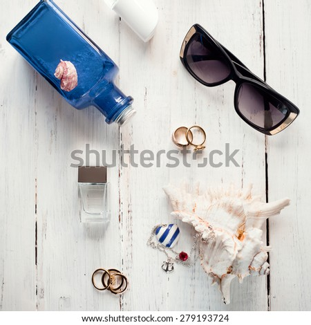 Set of female summer accessories (perfume, sunscreen, sunglasses, jewelry) with seashells on wooden background. Marine style fashion, vacation beach holiday, shopping, skin sun protection concepts. - stock photo