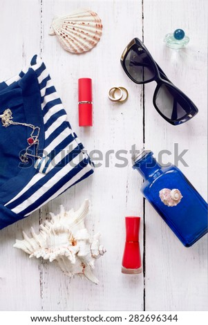Set of female summer accessories (red lipstick, nail polish, sunglasses, jewelry) and striped top or T-shirt, with seashells. Marine style fashion, vacation and beach holiday, shopping concepts. - stock photo