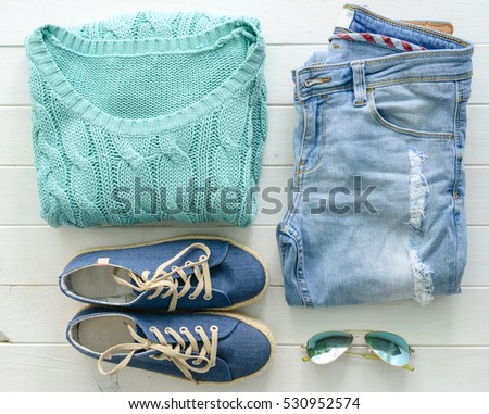 set of folded casual women clothes on wooden table top view