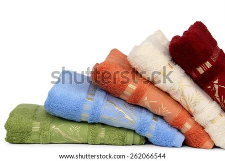 Set of folded colorful towels, isolated on white background - stock photo