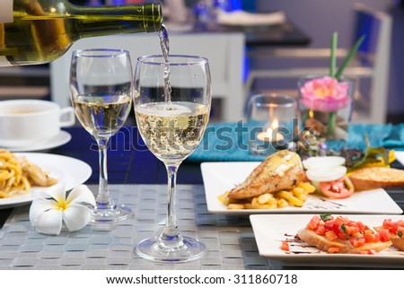 Set of food and Tasting-White wine pour in a glass on foods table - stock photo