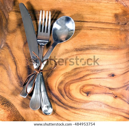 Set of fork, spoon and knife on wooden table
