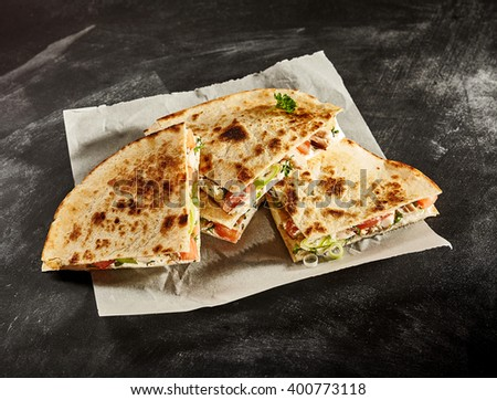 Set of four delicious cooked wheat tortilla quesadillas stuffed with onion, tomato and herbs in wax paper on dark background - stock photo