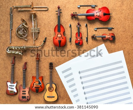 Set of four guitars, five golden brass wind and four string musical orchestra instruments: saxophone, trumpet, french horn, trombone, violin, cello, contrabass, viola and sheet music lying near it. - stock photo