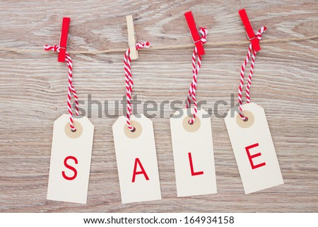 set of four sale tags hanging on wooden background - stock photo