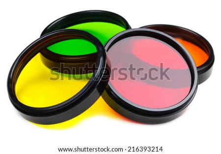 Set of four various colors photofilters for SLR camera. Close-up. Isolated on white background. - stock photo