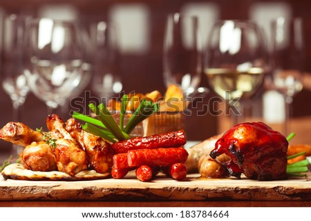 Set of fried meat and small meat sausages served with scallion and dried herbs on wooden cutting board with fried potato pieces.