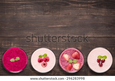 Set of fruit smoothie in glasses on wooden background - stock photo