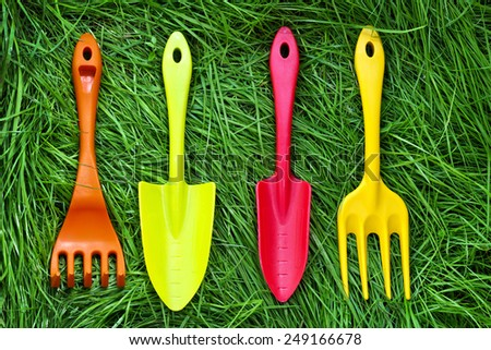 Set of gardening tools on green grass background. Plastic mini shovels, forks and spade. - stock photo