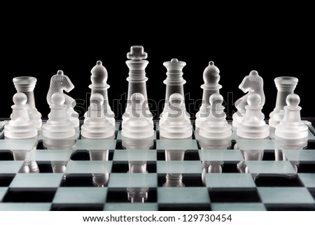 Set of glass chess pieces over black - stock photo