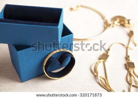 set of Golden  jewelries and gift box over white background. Christmas and accessories concept. Studio shot, horizontal