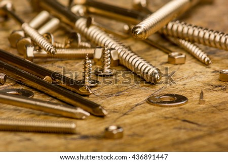 Set of golden screws, bolts, nails, washers, nuts on wooden background