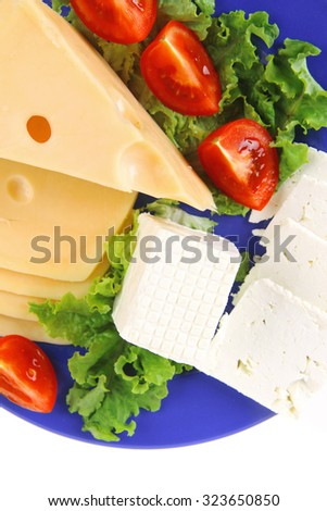 set of gourment delicatessen cheese slice and chunk ( bar)  white goat greek yellow french aged on green lettuce salad with tomatoes on blue plate isolated over white background - stock photo