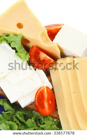 set of gourmet cheese slice and chunk ( bar)  white goat greek yellow french aged on half of rye bread on green lettuce salad with tomatoes on blue plate isolated over white background