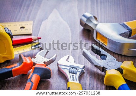 set of hand tools claw hammer pliers adjustable wrench nippers roulette pencil ruller  on wooden board construction concept  - stock photo