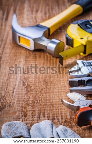 set of handtools hammer tapeline wrench pliers nippers glove on vintage wooden board construction concept  - stock photo