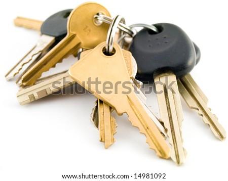 Set of House and Vehicle Keys on White Background - stock photo