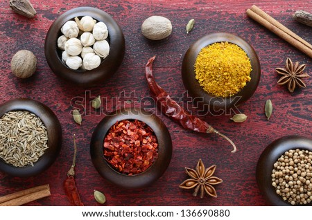 Set of Indian spices - cumin, chili, yellow nut spicy mix, coriander, white, black and green cardamon, nutmeg, cinnamon and star anise and on rusted wooden background - stock photo