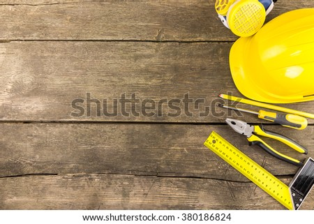 Set of industrial protective and work carpenter tools laid out on a rustic wooden table with copy space  including try square, screwdriver, pliers protective helmet, respirator and carpenter pencil. - stock photo