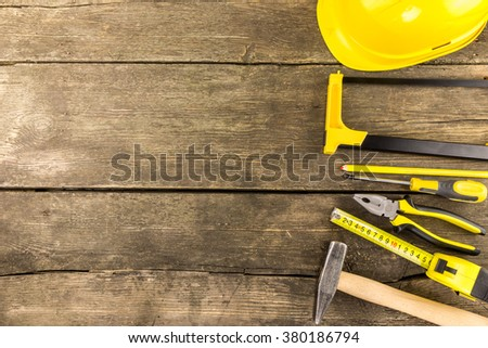Set of industrial work  tools laid out on a rustic wooden table with copy space  including measuring tape, screwdriver, pliers protective helmet, carpenter pencil, hammer and a hacksaw. - stock photo