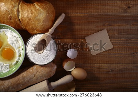 Set of ingredients and appliances for baking with yolk in flour and recipe on wooden table top, horizontal picture - stock photo
