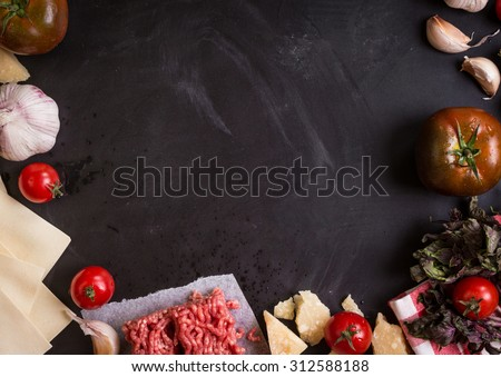 Set of ingredients for italian lasagna. Black food background with free space for text. Pasta, tomatoes, ground meat, parmesan, mozzarella, basil, garlic on a rustic chalkboard. Overhead - stock photo