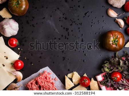 Set of ingredients for italian lasagna. Black food background with free space for text. Pasta, tomatoes, fresh ground meat, parmesan, mozzarella, basil, garlic on a rustic chalkboard. Overhead - stock photo