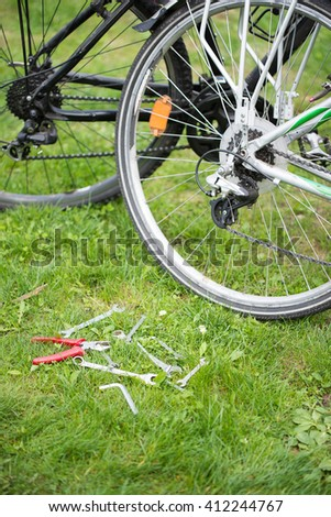 set of keys to repair the bike lying on the grass.