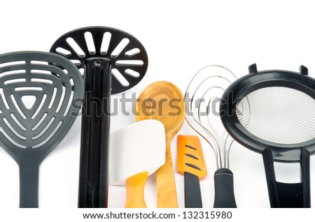 Set of Kitchen Utensils with Slotted Spoon, Potato Musher, Spatula, Wooden Spoon, Cream Spatula, Wire Whisk and Colander isolated on white background - stock photo