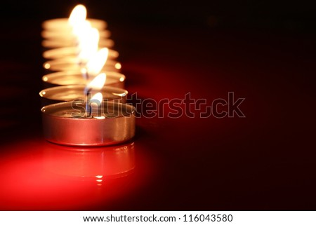 Set of lighting candles in a row on dark background with free space for text - stock photo