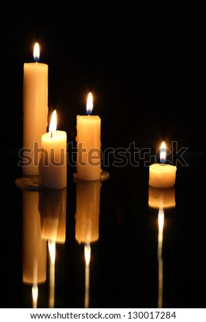 Set of lighting candles in a row on dark background with reverberation - stock photo
