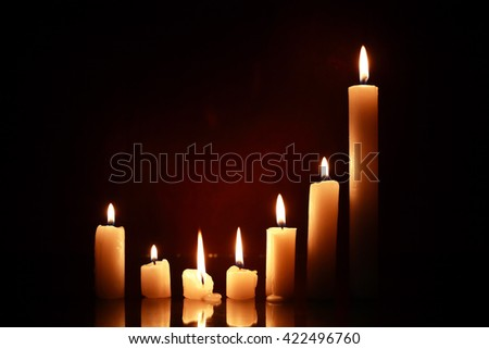 Set of lighting candles on nice dark background - stock photo