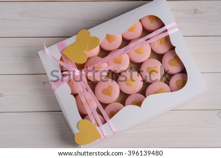 Set of macarons with golden hearts in a paper box with pink ribbons on white wooden table. Foreground photo. - stock photo