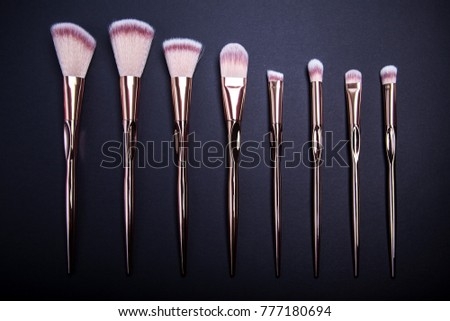 Set of make-up brushes for beautiful make-up looks on black background. Row of golden metal brushes.