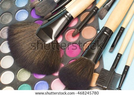 Set of make-up brushes on colorful eye shadows palette.